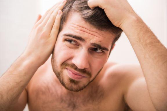 Man looking at his hair loss in the mirror.
