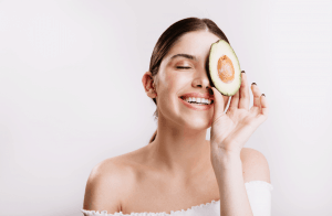 Woman holding avocado to eye.
