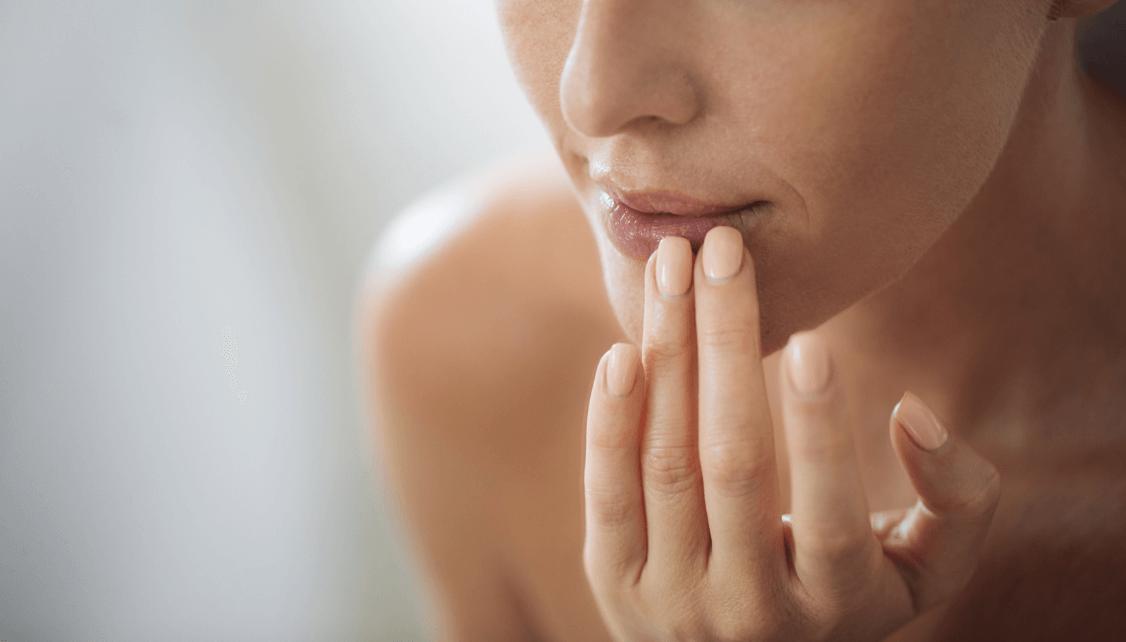 Close up of woman touching lips.