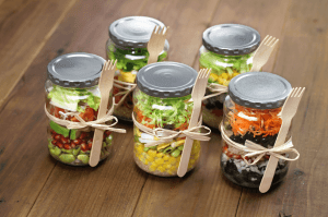 Mason jars filled with vegetables and fruit for meal prep.