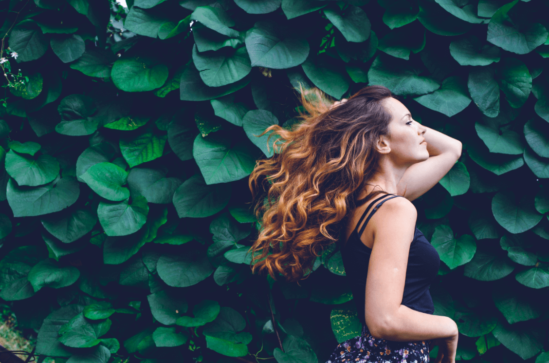 Side view of woman next to leaves with long curly hair.